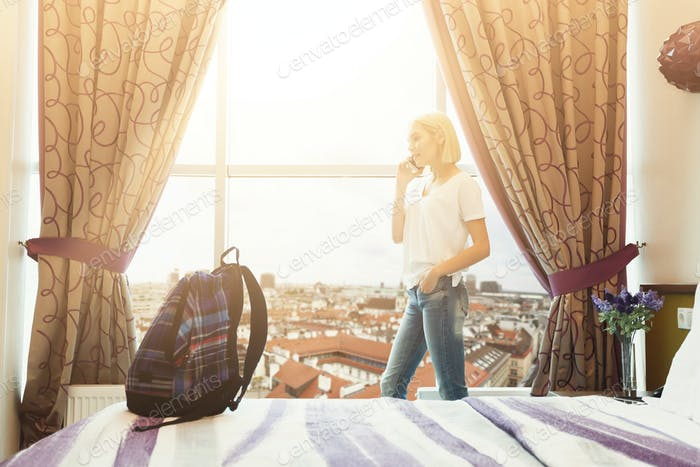 Woman standing near window in hotel room