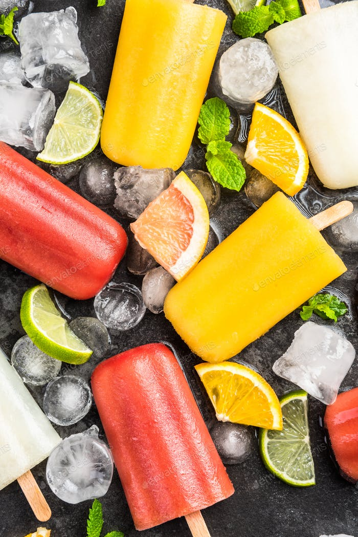 Natural juice homemade healthy popsicles over ice cubes