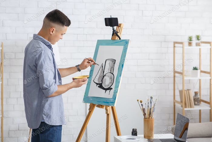 Art hobby and online lesson during COVID-19 epidemic. Young man draws abstract picture on easel with