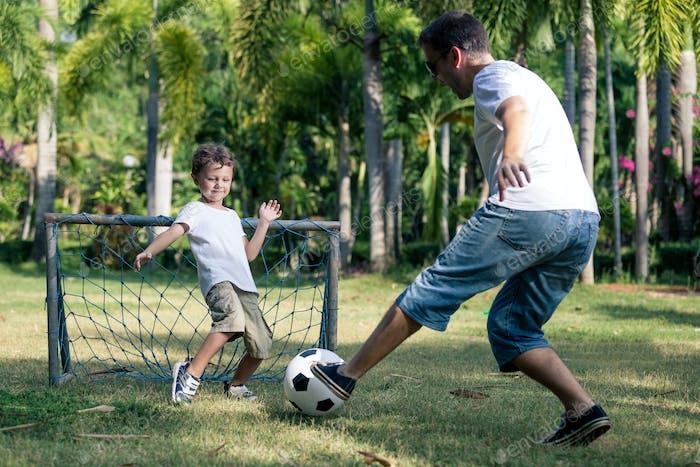 Vater und Sohn spielen im Park zur Tageszeit.