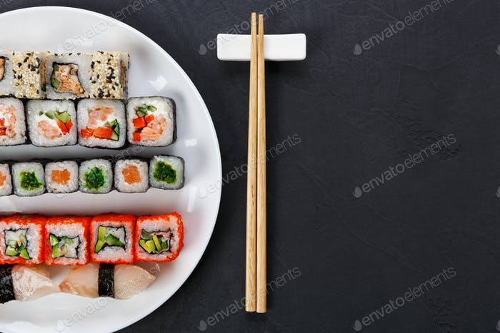Set of sushi and rolls on black background, top view