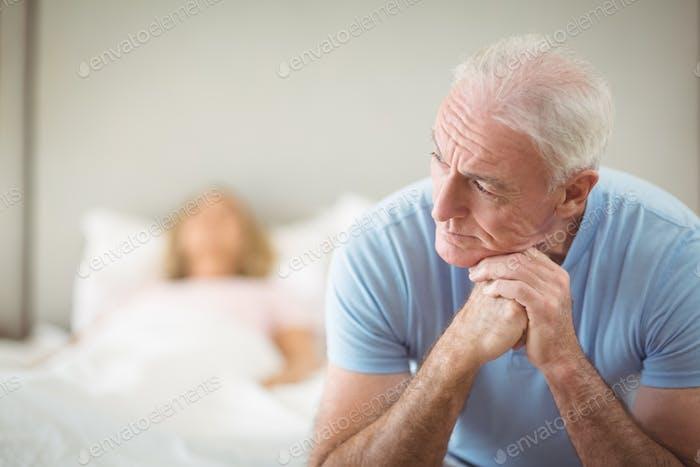 Worried senior man sitting in bedroom