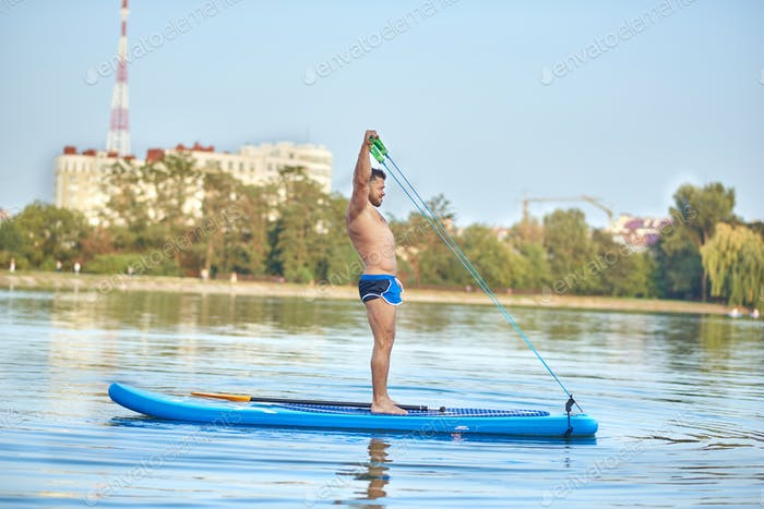 Sports boy doing streching exercise with expander on paddle board