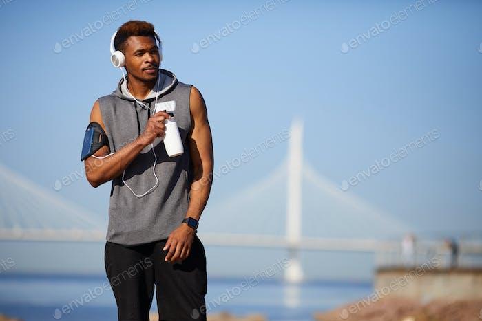 Black jogger drinking water