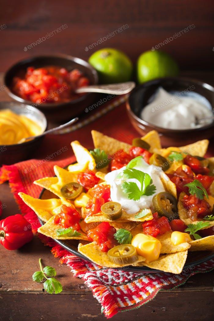 nachos cargados de salsa, queso y jalapeño