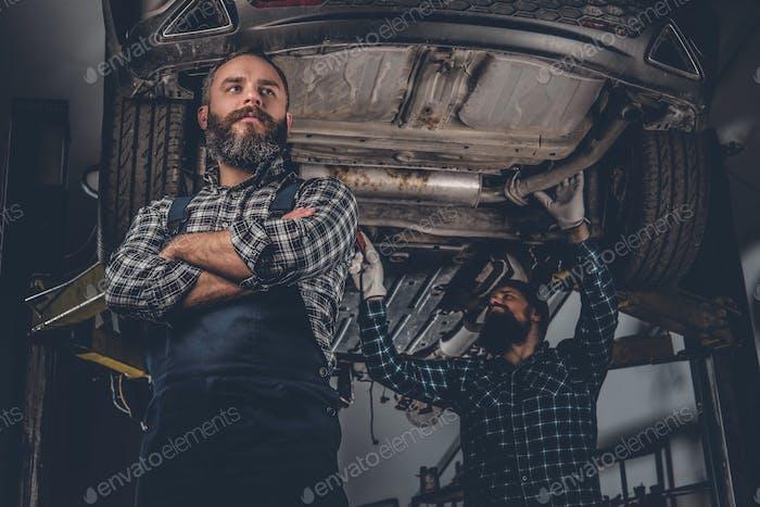 Zwei bärtige Mechaniker in einer Garage.