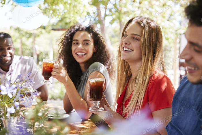 Young adult friends socialising at a table in a garden