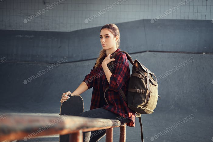 A student girl with a backpack wearing a checkered shirt
