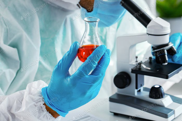 Medical worker in protective gown looking in microscope