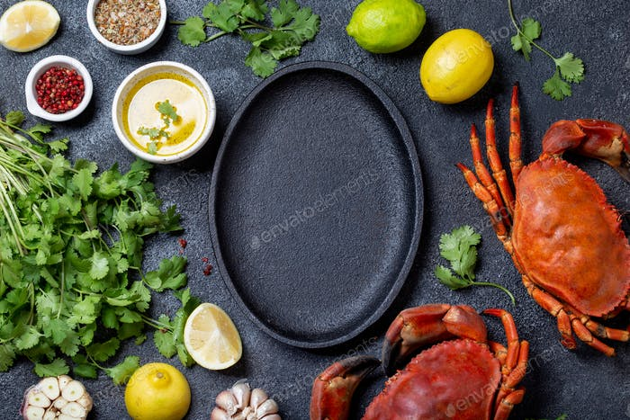 Food background with empty black plate, fresh crabs, lemons and herbs.