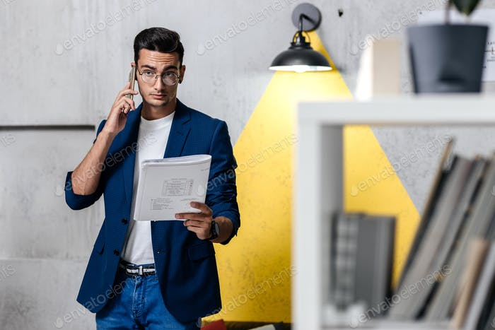 Architect dressed in stylish clothes talking by phone in a room with a stylish interior with
