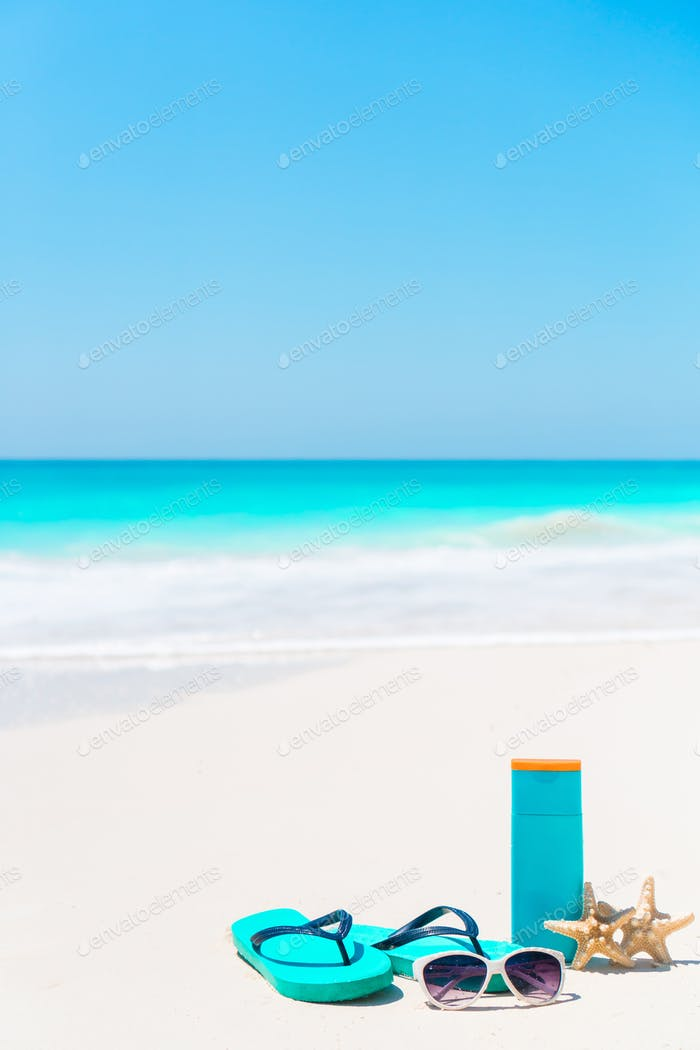 Beach accessories needed for sun protection. Suncream bottles, goggles, flip flops, starfish on