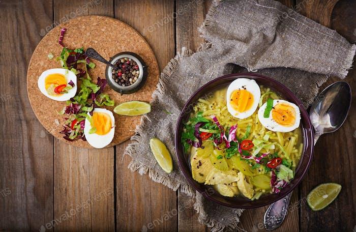 Nudelsuppe mit Huhn, Sellerie und Ei in einer Schüssel auf einem alten Holzhintergrund. Flache Lag. Draufsicht.