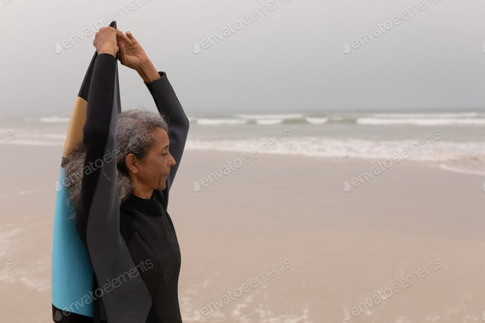 Side view of senior female surfer with arms up holding surfboard on the beach