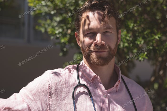 Portrait of confident Caucasian male doctor sitting on bench outside the nursing home