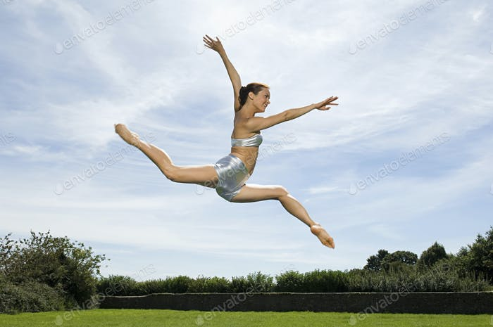 A young woman leaping in the air. Acrobat.