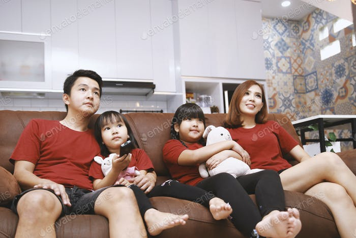 Asian Family Watching TV at Home