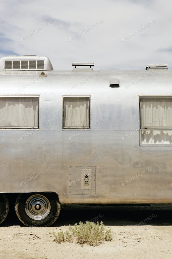 A vintage Airstream silver accommodation trailer parked on salt flats.