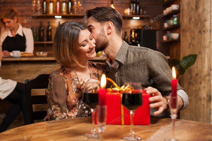 Attractive bearded man kissing his girlfriend cheek after recieving a birthday gift