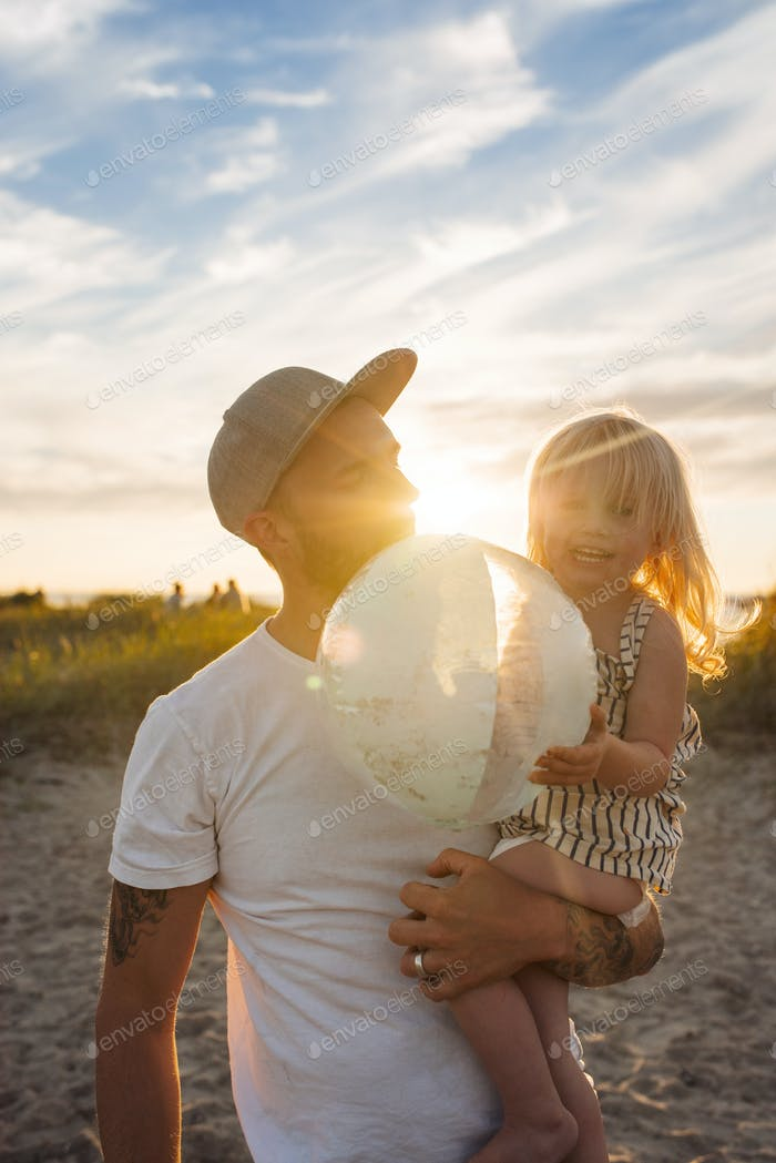 Father holding daughter (2-3) on beach at sunset