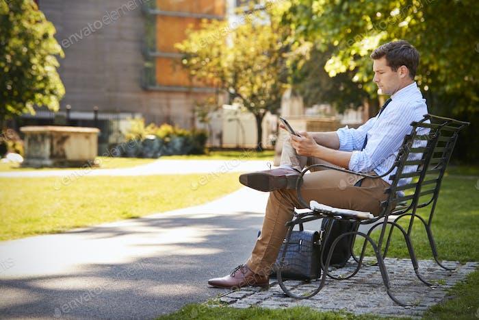 Businessman Outdoors Using Digital Tablet On Lunch Break In Park