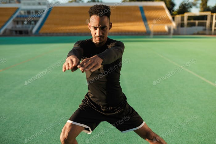 Young serious African American sportsman heavily doing exercises during workout at city stadium