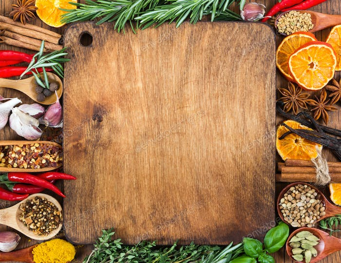 Different spices, seasonings and herbs on wooden background