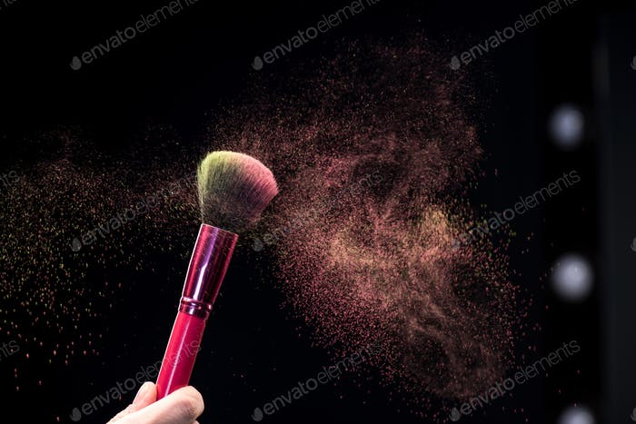 Partial view of female hand holding make-up brush with powder explosion on black