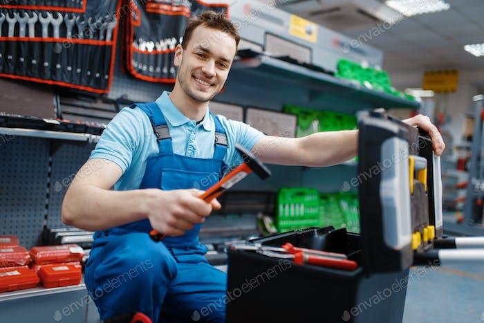 Happy male worker choosing toolbox in tool store