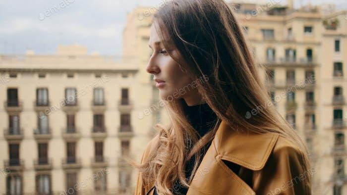 Красивая чувственная девушка задумчиво глядя на балкон с прекрасным видом на архитектуру