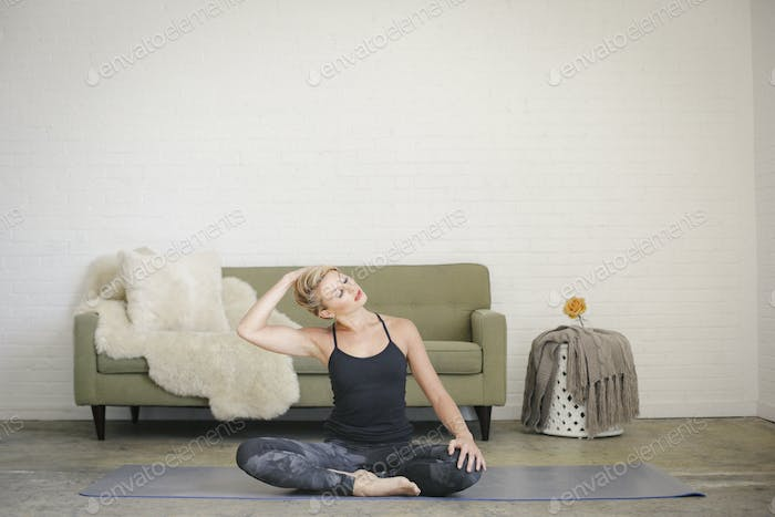 A blonde woman in a black leotard and leggings, sitting on a yoga mat in a room. .