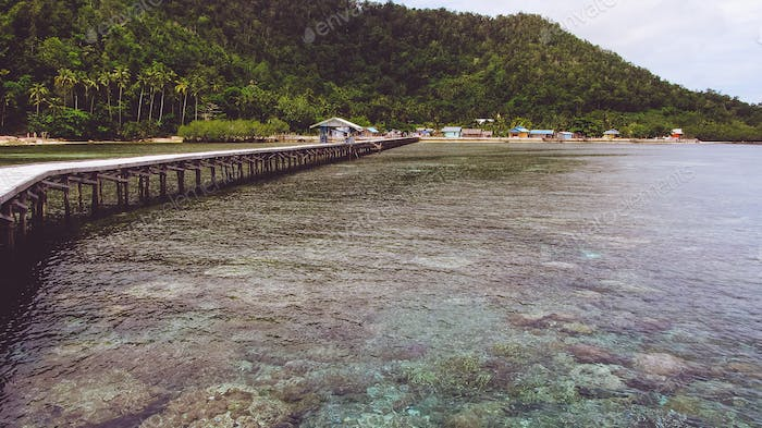 Wooden jetty near Yenbuba village leading to Mansuar island in Raja Ampat. Beautiful corals in