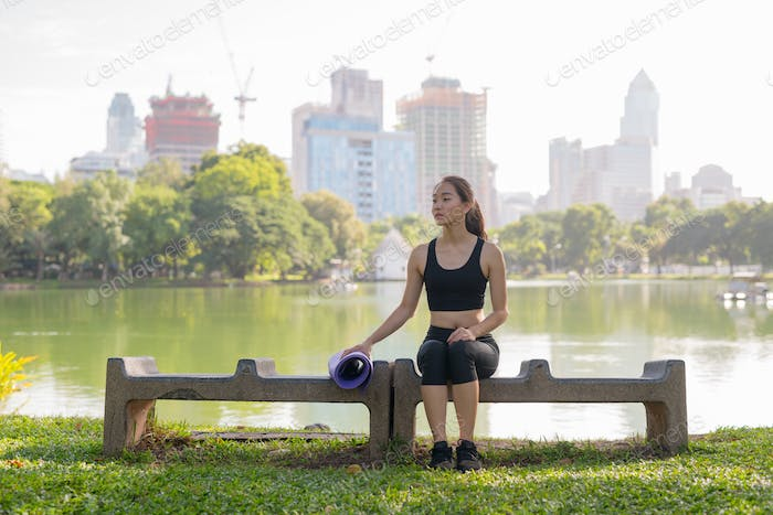 Beautiful Asian Woman Sitting In Park And Thinking