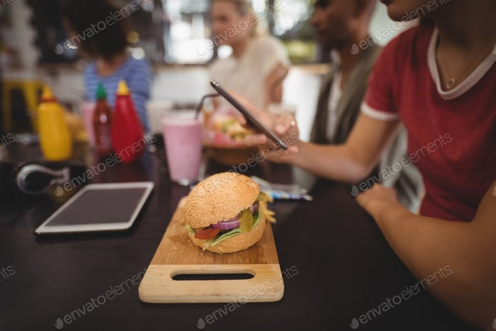 Midsection of young woman using smartphone while sitting with burger