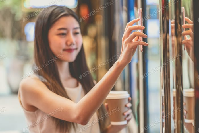 Closeup asian young woman hand using smart mobile phone scanning the movie tickets machine