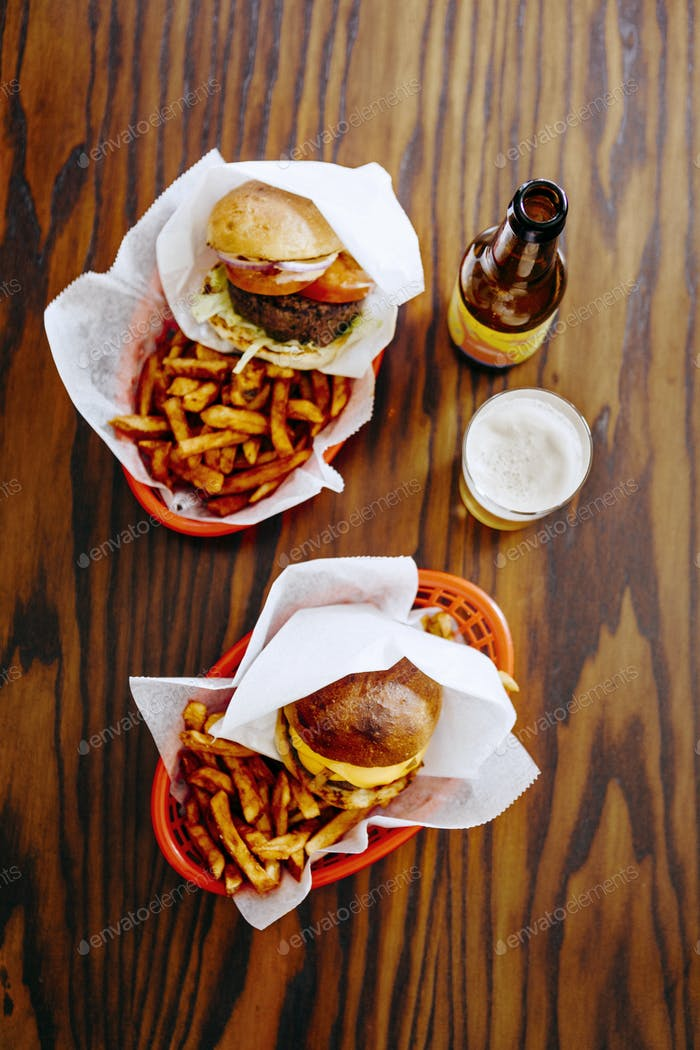Directly above shot of fast foods served with beer on restaurant table