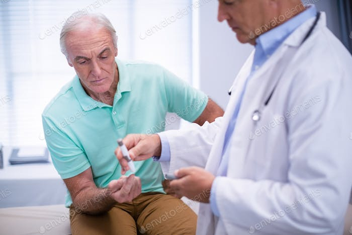 Doctor examining senior patient blood sugar
