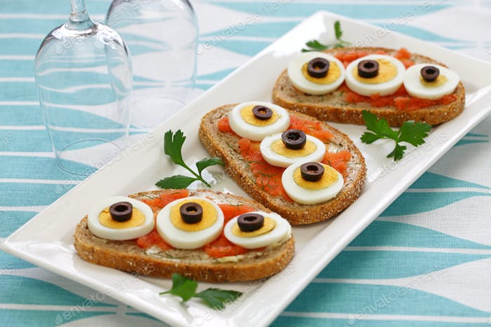 sliced boiled egg, black olives and dill on top of seasoned cod roe rye bread.