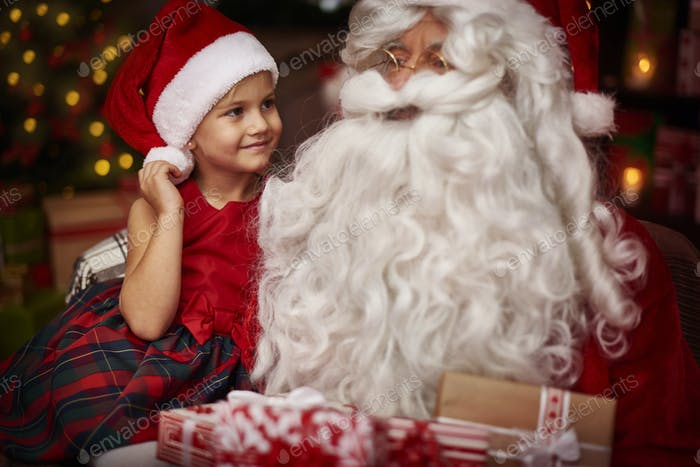 Cute girl sitting on the santa's knees
