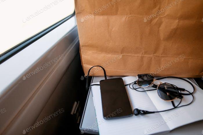 Telefon mit Kopfhörern am Notebook an der Fensterleuchte im Zug