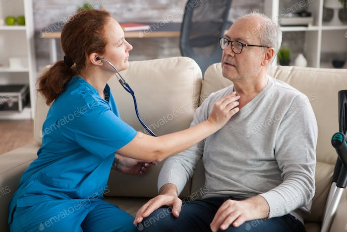 Pretty female nurse using stethoscope to listen the heart of old man