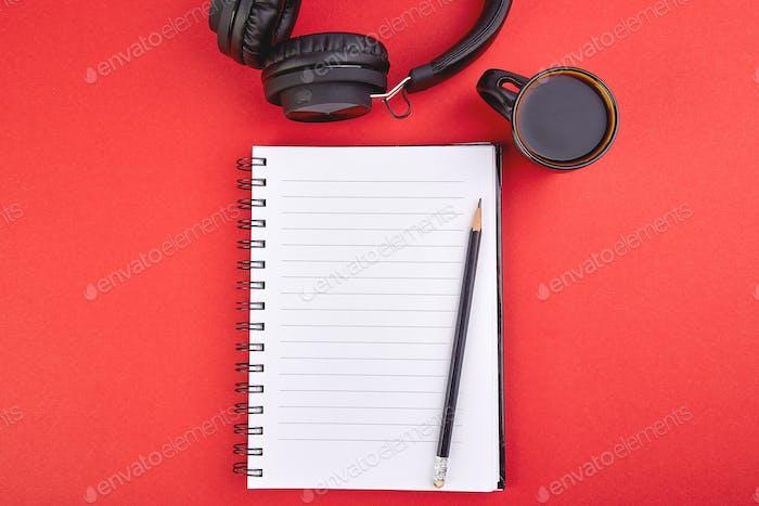 Schwarze Kopfhörer und Tasse Kaffee mit Notebook,