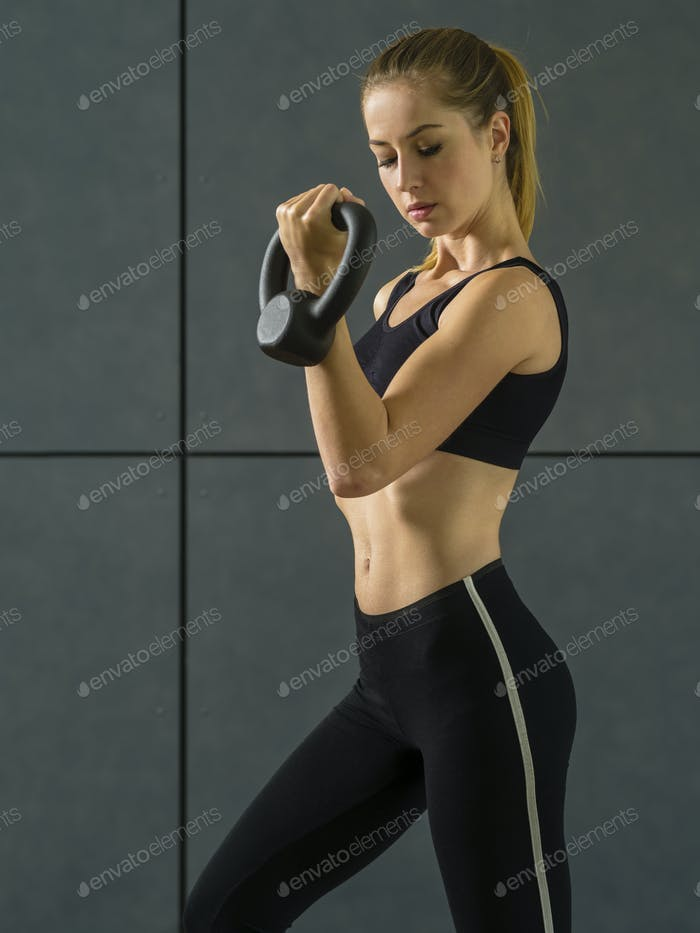 Young woman doing bicep curls with kettlebell
