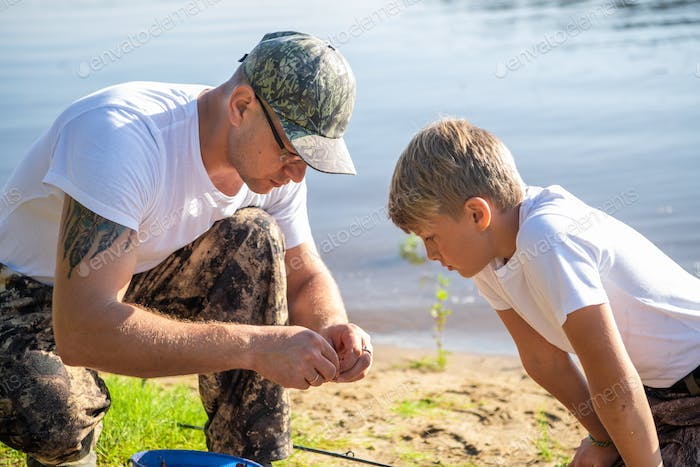 Teamwork. Father and son fishing on a summer weekend. Hobby and sport activity, preparing fish bait