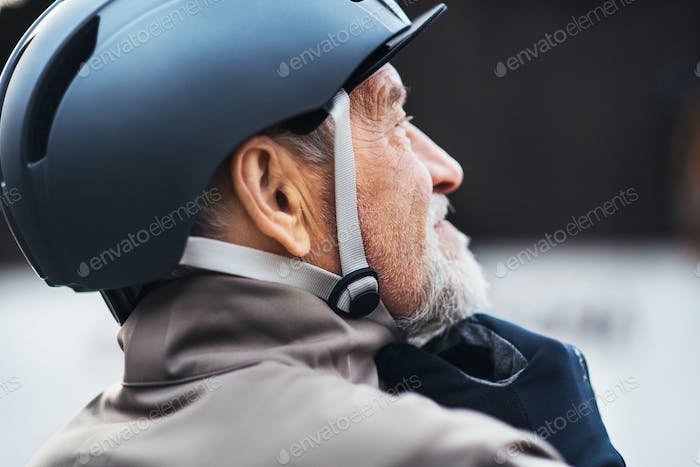 Close-up of active senior man standing outdoors in town, putting on a bike helmet.