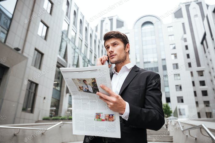 Pensive young businessman talking on mobile phone and reading newspaper