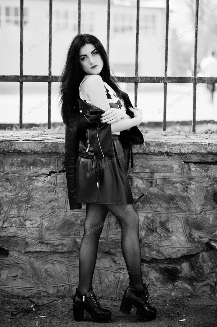 Young goth girl on black leather skirt, jacket and high heels punk shoes against iron fence.