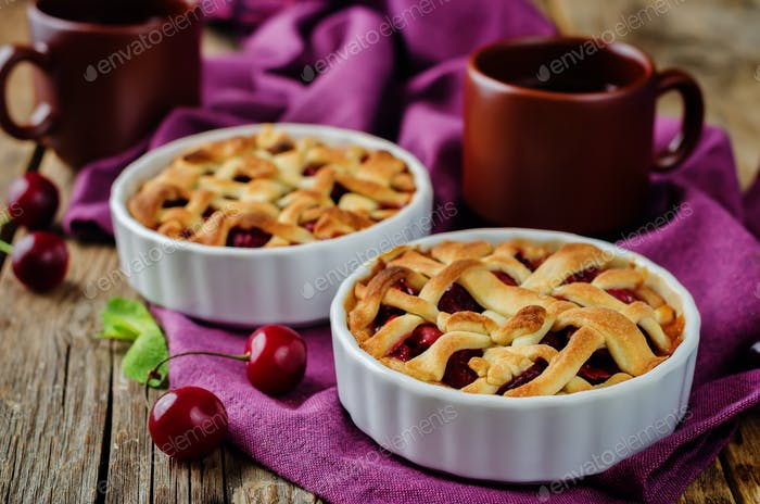 Cherry pies with fresh cherries oand cups of tea