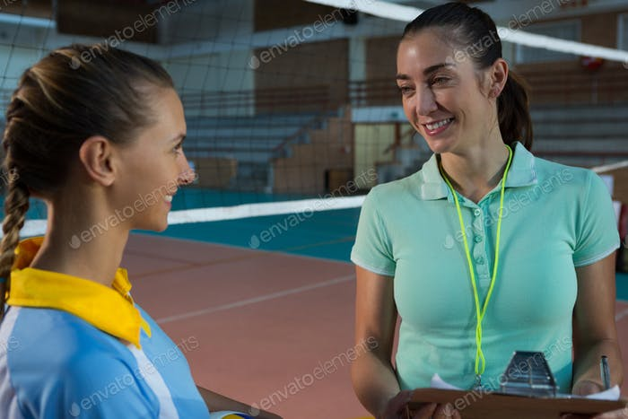 Female coach talking with volleyball player