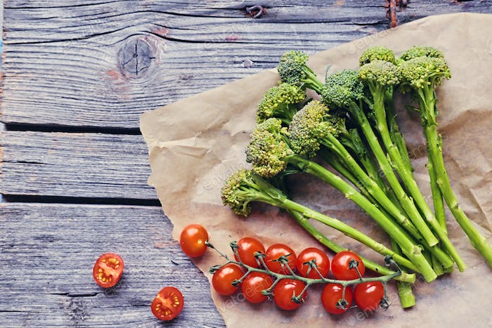 Tomatoes and broccoli on a wooden table.